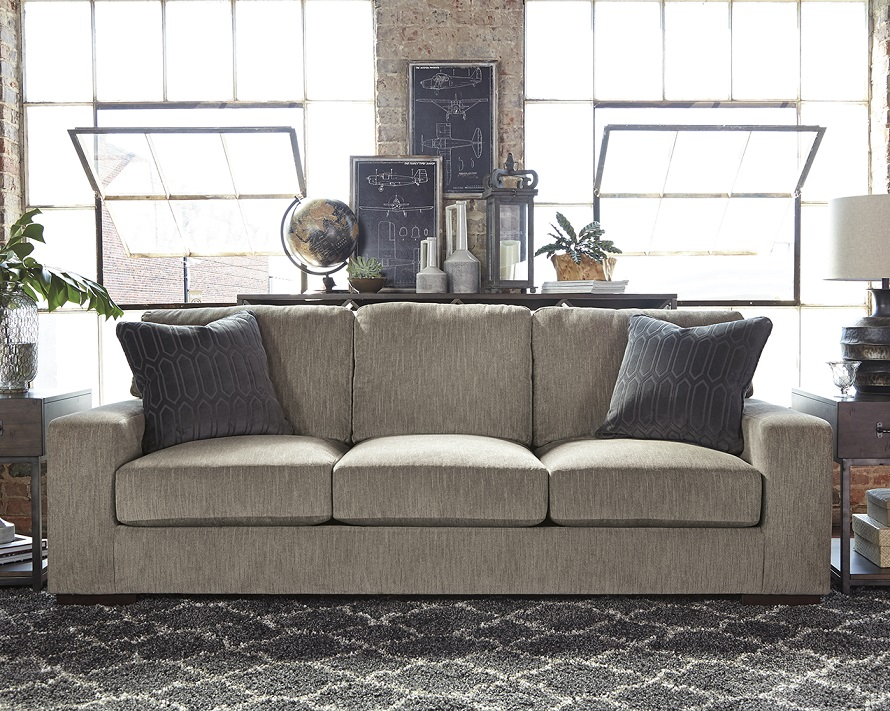 Gray track arm syled sofa with dark pillows and a black chevron rug underneath.