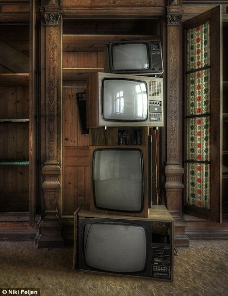 A stack of old television sets of different sides and front different eras